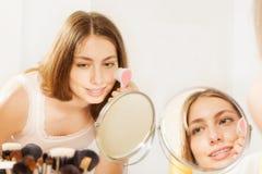 Attraktive junge Frau, die Hautreinigungsbürste verwendet stockfoto