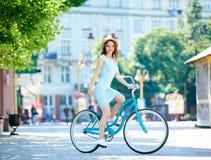 Attraktive junge Frau, die ihr Fahrrad fahrend genießt stockfoto