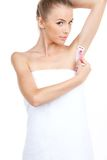 Attraktive junge Frau, die ihre Achselhöhlen rasiert stockbild
