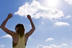 Attraktive junge Frau, die ihre Arme bei der Stellung gegen einen tiefen blauen Himmel ausdehnt Stockbild