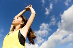 Attraktive junge Frau, die ihre Arme bei der Stellung gegen einen tiefen blauen Himmel, trainierend an einem sonnigen Tag ausdehn Lizenzfreies Stockbild