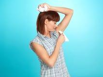 Attraktive junge Frau, die ihren Achselhöhleschweiß abwischt Lizenzfreie Stockfotografie