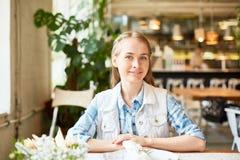 Attraktive junge Frau, die im Café und im Lächeln sitzt stockfoto