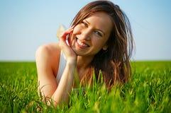 Attraktive junge Frau, die im grünen Gras liegt Stockfotos