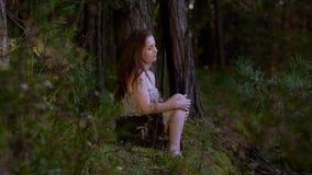 Attraktive junge Frau, die im Wald allein sitzt stock video footage