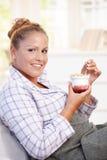 Attraktive junge Frau, die Joghurt im Bett isst Lizenzfreie Stockbilder