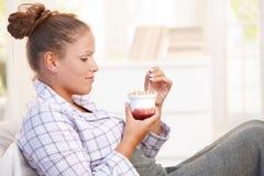 Attraktive junge Frau, die Joghurt im Bett isst Stockbild