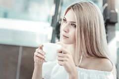 Attraktive junge Frau, die Kaffee trinkt Stockfotografie
