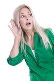Attraktive junge Frau, die - lokalisiert auf Weiß heimlich zuhört. Lizenzfreie Stockfotografie