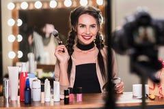 Attraktive junge Frau, die Make-up beim blogging tut Lizenzfreies Stockfoto
