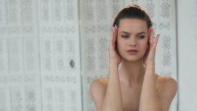 Attraktive junge Frau, die Massage auf Gesicht und Kinn in ihrem Badezimmer tut stock video footage