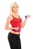 Attraktive junge Frau, die mit Gewichten trainiert Lizenzfreie Stockfotos