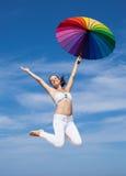 Attraktive junge Frau, die mit Sonnenschirm springt Stockfotos