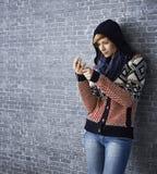 Attraktive junge Frau, die MP3-Player verwendet Stockfotos