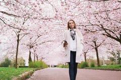 Attraktive junge Frau, die Musik am Frühlingsblütengarten genießt Stockfoto