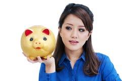 Attraktive junge Frau, die piggy Querneigung anhält Stockfotografie