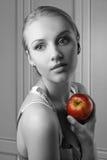 Attraktive junge Frau, die roten Apfel anhält Lizenzfreies Stockfoto