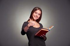 Attraktive junge Frau, die sich Daumen zeigt Stockfoto