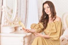 Attraktive junge Frau, die Spiegel betrachtet Stockbilder