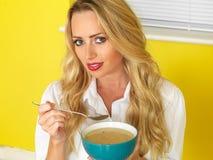 Attraktive junge Frau, die Suppe isst Stockbilder