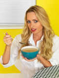 Attraktive junge Frau, die Suppe isst Stockfotos
