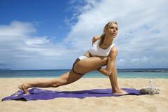 Attraktive junge Frau, die Yoga auf Strand tut Lizenzfreies Stockfoto