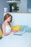 Attraktive junge Frau, die zu Hause einen Laptop verwendet Lizenzfreie Stockfotos
