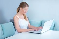 Attraktive junge Frau, die zu Hause einen Laptop verwendet Stockfotografie