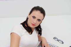 Attraktive junge Frau, die zu Hause an ihrem Laptop arbeitet Stockfoto