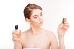Attraktive junge Frau, die zwei Flaschen parfums hält Stockfoto