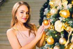 Attraktive junge Frau in einem eleganten Glättungskleid des Rosas, das in einer schicken Halle nahe Weihnachtsbaum mit gelbem Bal stockbilder