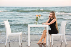 Attraktive junge Frau in einem eleganten und schwarzen Kleid sitzt an einem Tisch auf dem Hintergrund des Meeres Stockbild