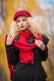 Attraktive junge Frau in einem Herbstmodetrieb. Schönes modernes junges Mädchen mit dem roten Zubehör im Freien Lizenzfreies Stockfoto
