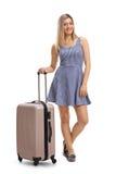 Attraktive junge Frau in einem Kleid mit einem Koffer Lizenzfreie Stockfotos