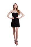 Attraktive junge Frau in einem schwarzen Kleid lächelnd und c betrachtend Stockbild