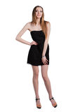 Attraktive junge Frau in einem schwarzen Kleid lächelnd und c betrachtend Stockfoto
