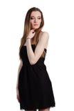 Attraktive junge Frau in einem schwarzen Kleid lächelnd und c betrachtend Lizenzfreies Stockfoto
