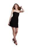 Attraktive junge Frau in einem schwarzen Kleid lächelnd und c betrachtend Stockfotos