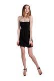 Attraktive junge Frau in einem schwarzen Kleid lächelnd und c betrachtend Stockbilder