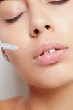Attraktive junge Frau erhält kosmetische Einspritzung Stockfoto