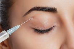 Attraktive junge Frau erhält kosmetische Einspritzung Stockfotografie
