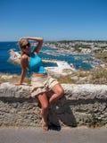 Attraktive junge Frau im Bikini, der auf dem Poolside liegt und an der Kamera lächelt Stockfoto