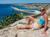 Attraktive junge Frau im Bikini, der auf dem Poolside liegt und an der Kamera lächelt Stockfotos