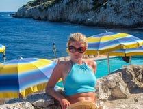 Attraktive junge Frau im Bikini, der auf dem Poolside liegt und an der Kamera lächelt Stockbild