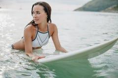 attraktive junge Frau im Bikini, der auf Surfbrett sich entspannt stockfotografie