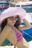 Attraktive junge Frau im Bikini und im rosafarbenen Hut durch den Hafen Stockbild
