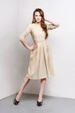 Attraktive junge Frau im goldenen Kleid steht in Mode Haltung Stockfotos