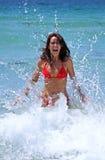 Attraktive junge Frau im roten Bikini, der durch eine kalte blaue Kristallwelle auf dem Strand gespritzt wird Lizenzfreie Stockbilder