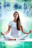 Attraktive junge Frau im weißen Meditieren am See stockfoto
