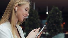 Attraktive junge Frau lächelt, arbeitend mit einer Tablette in den Kopfhörern stock footage